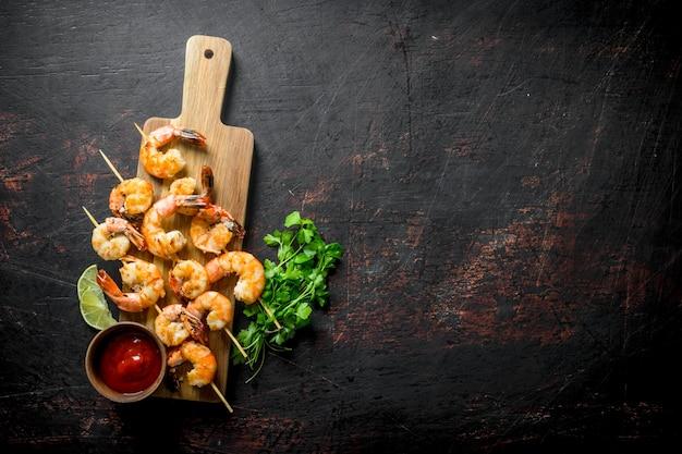 Gotowane krewetki na drewnianej desce do krojenia z sosem i ziołami na ciemnym drewnianym stole