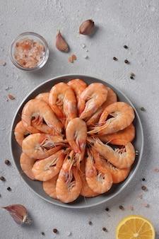 Gotowane krewetki na okrągłym talerzu z przyprawami na jasnoszarej powierzchni.