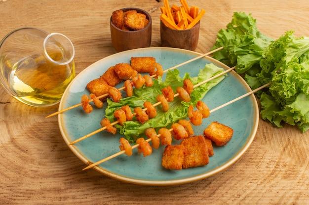 Gotowane krewetki na paluszkach wewnątrz niebieskiego talerza z zieloną sałatą i olejem na drewnie