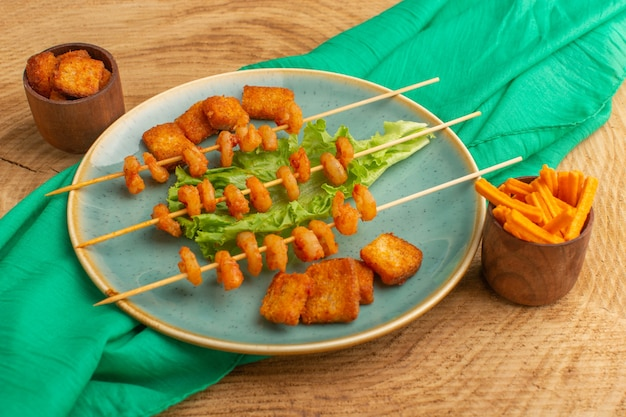 Gotowane krewetki na paluszkach wewnątrz niebieskiego talerza z zieloną sałatą na drewnie
