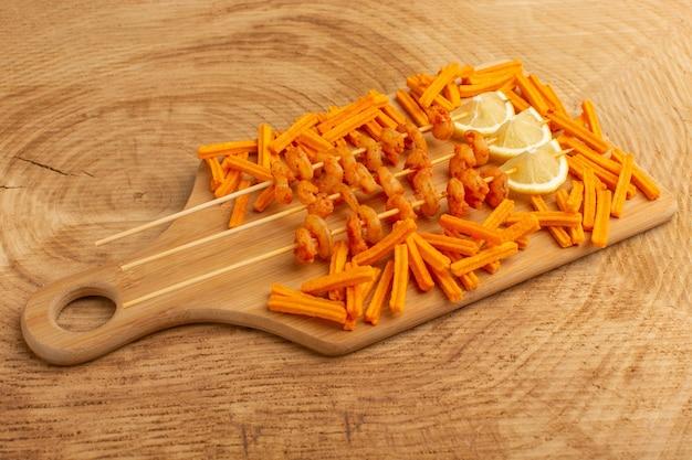 Gotowane krewetki na paluszkach z plasterkami cytryny i sucharkami na drewnianym biurku