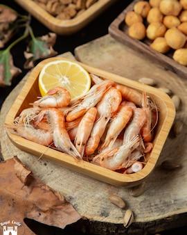 Gotowane krewetki w talerzu podawane z cytryną