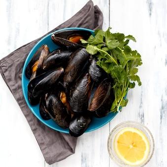 Gotowane małże, niebieski talerz, szara serwetka z ziołami i cytryną na drewnianym stole
