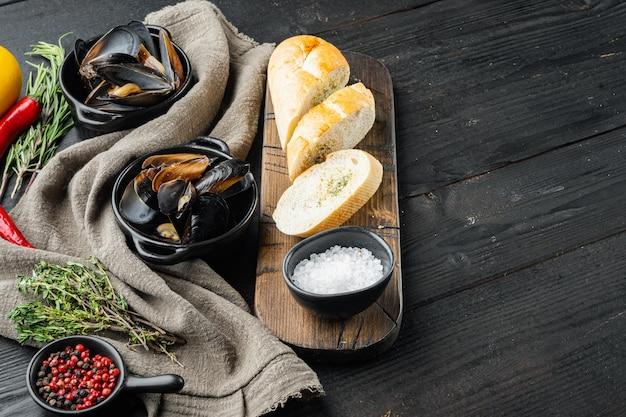 Gotowane małże z natką pietruszki, przyprawami i chlebem, na tle czarnego drewnianego stołu, z copyspace i miejsca na tekst