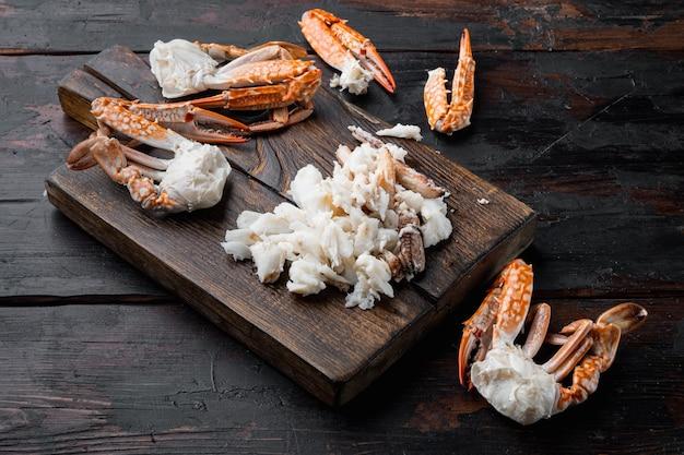 Gotowane mięso kraba pływaka niebieskiego lub krab niebieski koń, zestaw krabów kwiatowych, na drewnianej desce do krojenia, na ciemnym tle drewnianych