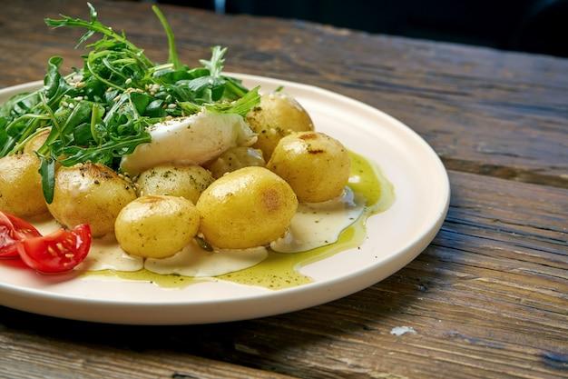 Gotowane młode ziemniaki z sałatką z rukoli i jajko sadzone doprawione sosem śmietanowym na drewnianym