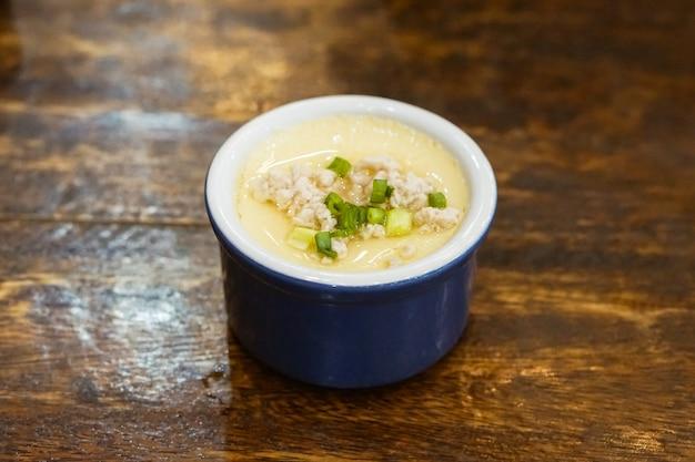 Gotowane na parze jajko (kai thoon) (tajskie potrawy), chawanmushi (japońskie potrawy) w niebieskiej misce.