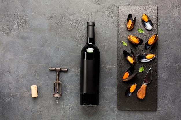 Gotowane na płasko małże w łupku z butelką wina