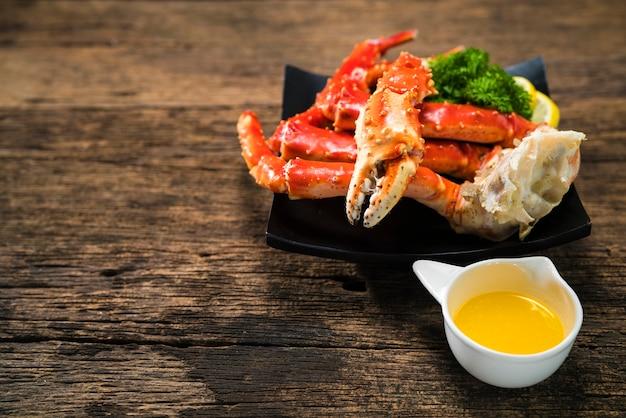 Gotowane organiczne nogi kraba alaskan king z masłem i cytrynami, alaskan king crab na vintage drewniane tła.