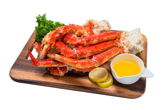 Gotowane organiczne nogi kraba królewskiego z alaski z masłem i cytrynami, krab królewski z alaski na drewnianym talerzu
