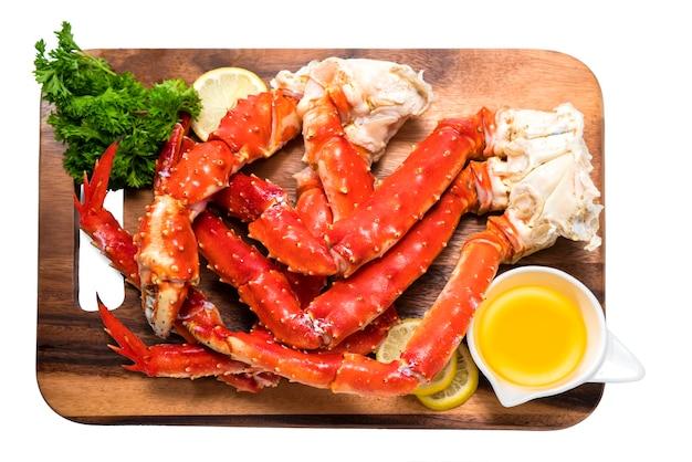 Gotowane organiczne udka kraba królewskiego z alaski z masłem i cytrynami na drewnianym talerzu