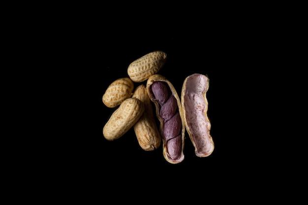 Gotowane orzeszki ziemne (amendoin cozido, sergipe, nordeste, brazylia) na czarnym tle. niektóre otwarte, inne zamknięte.