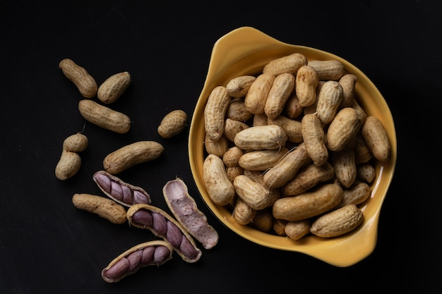 Gotowane orzeszki ziemne (amendoin cozido, sergipe, nordeste, brazylia) w czarno-żółtej misce i gotowane orzeszki ziemne rozłożone i otwarte na zewnątrz miski na czarnym tle. widok z góry.
