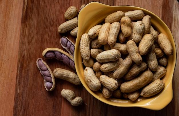 Gotowane orzeszki ziemne (amendoin cozido, sergipe, nordeste, brazylia) w czarno-żółtej misce i gotowane orzeszki ziemne rozłożone i otwarte na zewnątrz miski na drewnianym tle. widok z góry.
