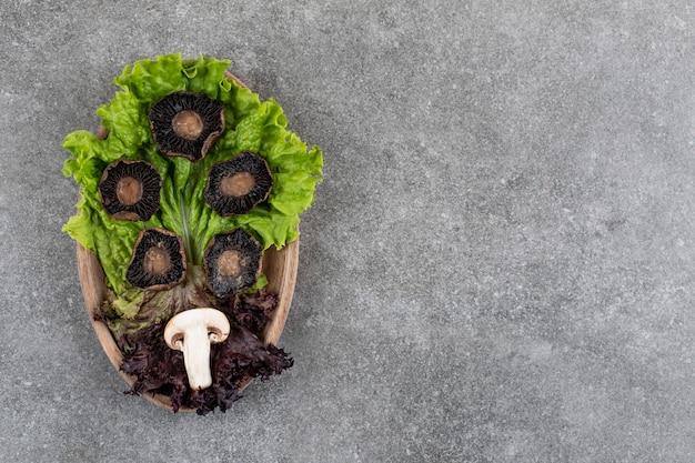 Gotowane pieczarki z synem zielonym drewnianym talerzu.