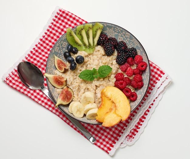 Gotowane płatki owsiane z owocami w okrągłym talerzu na białym stole, zdrowe śniadanie. widok z góry