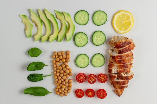 Gotowane składniki na dietetyczną sałatkę z kurczakiem, pomidorem z ogórkiem awokado i szpinakiem