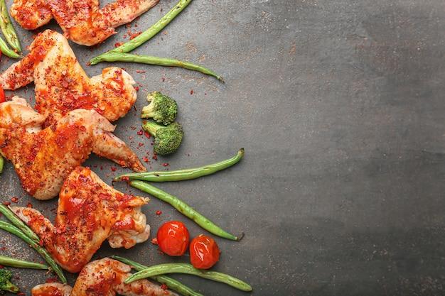 Gotowane skrzydełka z kurczaka z warzywami na ciemnym stole