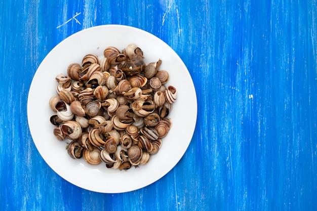 Gotowane ślimaki na białym talerzu na niebieskim drewnianym