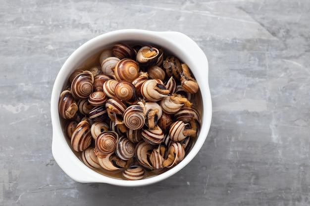 Gotowane ślimaki w białej misce na ceramicznym tle
