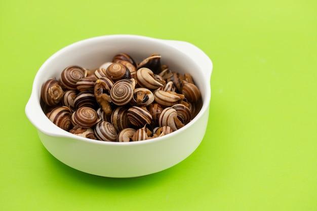 Gotowane ślimaki w białej misce na zielonym tle