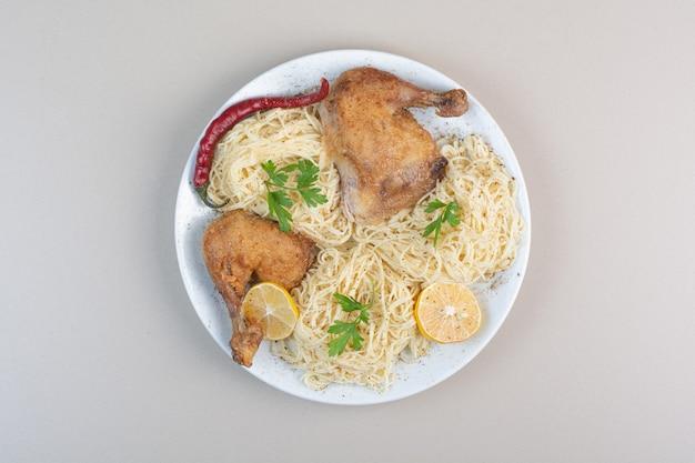 Gotowane spaghetti, papryka i udka z kurczaka na białym talerzu