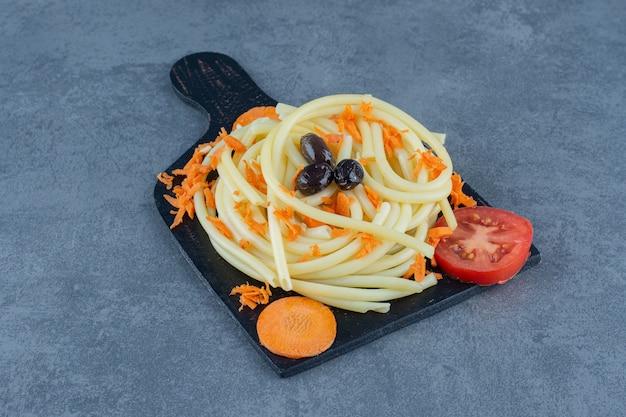 Gotowane spaghetti z warzywami na czarnej tablicy.