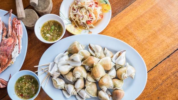 Gotowane świeże canarium laevistrombus lub ślimak morski z surową sałatką z mango i ostrymi owocami morza sa