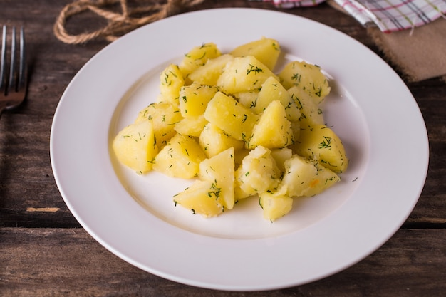 Gotowane ziemniaki z koperkiem na białym talerzu na rustykalnym stole drewna