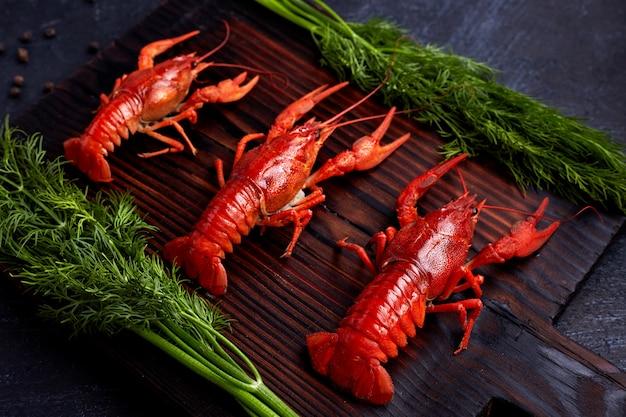 Gotowani gotowani rakowi raki przygotowywający jeść na ciemnym drewnianym tle. skopiuj miejsce nad głową.