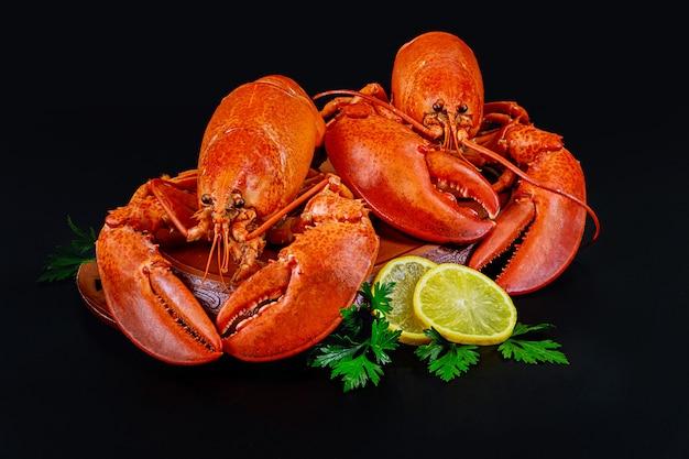 Gotowani homary z cytryną na czarnym tle