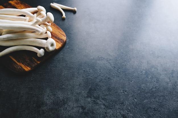 Gotowanie białych grzybów na ciemnoszarym tle. wysokiej jakości zdjęcie