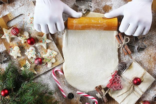 Gotowanie ciastek maślanych o różnych kształtach na drewnianym stole ze świątecznymi akcesoriami