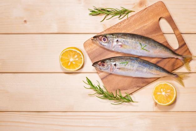 Gotowanie dań rybnych z różnymi składnikami. świeże surowe ryby ozdobione plasterkami cytryny i ziołami na drewnianym stole.