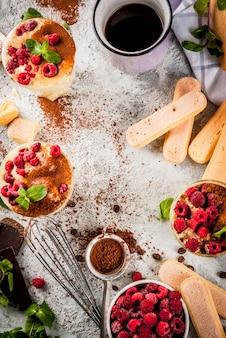 Gotowanie deseru z włoskiego jedzenia tiramisu, ze wszystkimi niezbędnymi składnikami: kakao, kawę, ser mascarpone, miętę i maliny, na szarej kamiennej powierzchni. widok z góry