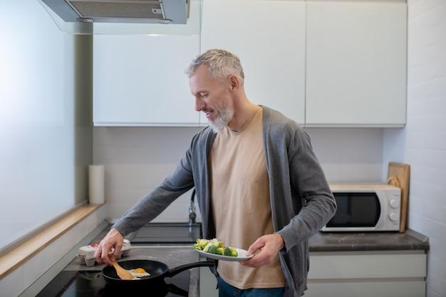 Gotowanie. dojrzały bered mężczyzna gotuje w kuchni