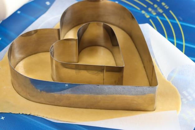 Gotowanie domowego ciasta w kształcie serca. rozwałkowanie ciasta na stole i krojenie za pomocą foremek