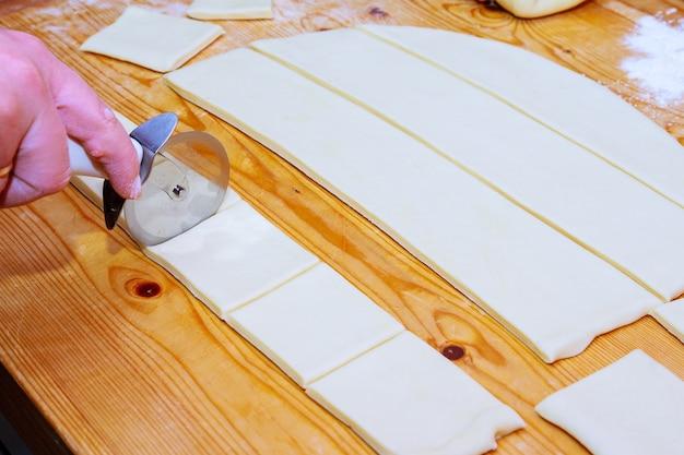 Gotowanie domowych bajgli. wyrabianie ciasta, krojenie i formowanie ciasta. rogaliki.