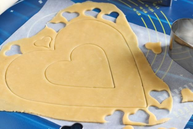 Gotowanie domowych ciasteczek w kształcie serca. rozwałkowanie ciasta na stole i krojenie za pomocą foremek