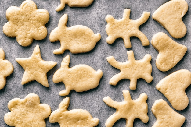 Gotowanie domowych ciasteczek w postaci zwierząt ułożonych na blasze do pieczenia na pergaminie, przysmaki świąteczne lub noworoczne, widok z góry