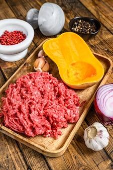 Gotowanie dyni z mięsem mielonym, czosnkiem i cebulą. drewniane tło. widok z góry.
