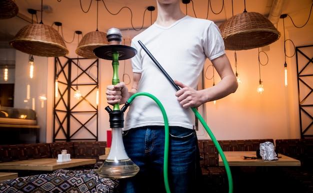 Gotowanie fajki wodnej w barze. młody człowiek z fajki w restauracji, fajki, palenie kawiarni.