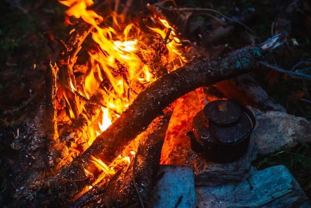 Gotowanie herbaty w czajniku na ognisku z dużym drewnem opałowym.