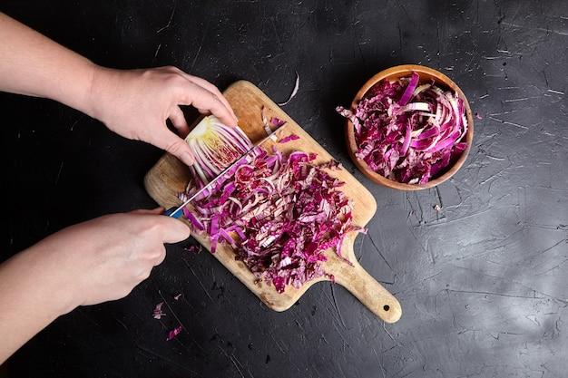 Gotowanie kapusty red napa. kobiece ręce z nożem, drewniana deska do krojenia i miska na stole, widok z góry