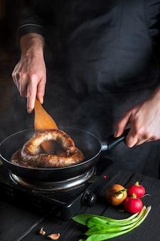 Gotowanie kiełbasy mięsnej w kuchni restauracji. kucharz lub gotuj smaży kiełbasę na patelni. pomysł na pyszną dietę mięsną