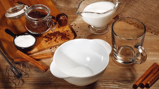 Gotowanie krok po kroku koreańskiej kawy dalgona. zestaw produktów: kawa rozpuszczalna, mleko, woda, cukier.