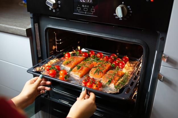 Gotowanie łososia w piekarniku. gospodyni przygotowuje obiad. szef kuchni gotuje czerwoną rybę. gotowanie ryb w piekarniku.
