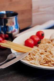 Gotowanie makaronu z pomidorami, stół kuchenny