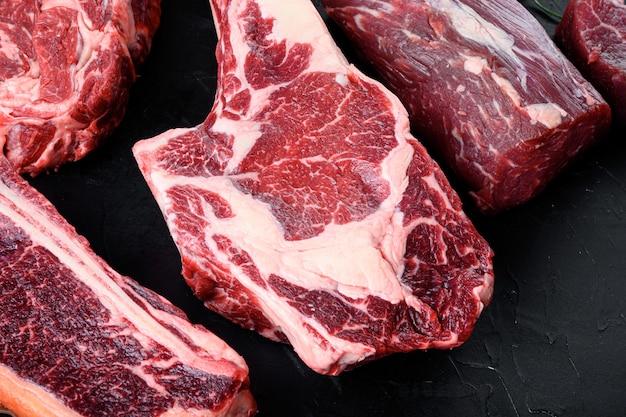 Gotowanie mięsa tło. surowy stek tomahawk, z przyprawami i ziołami do zestawu do gotowania, na czarnym kamiennym tle