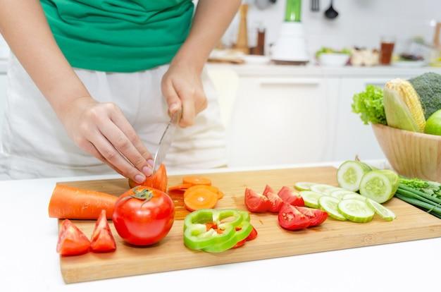 Gotowanie. młoda ładna kobieta w zielonej koszuli cięcia gotowania i nóż przygotowuje sałatkę ze świeżych warzyw na dobre zdrowe w kuchni w domu